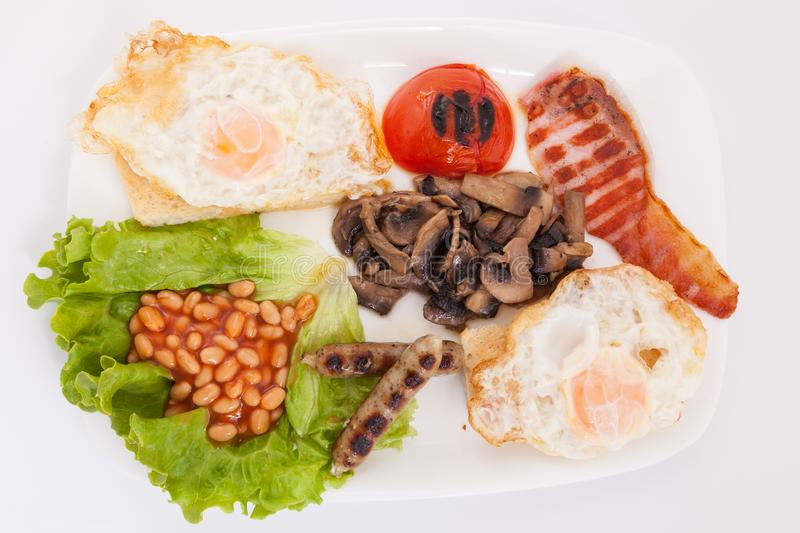 Full english breakfast view from above. Bean, eggs , bacon slices, sausages, tomatoe and mushrooms on white plate stock photo