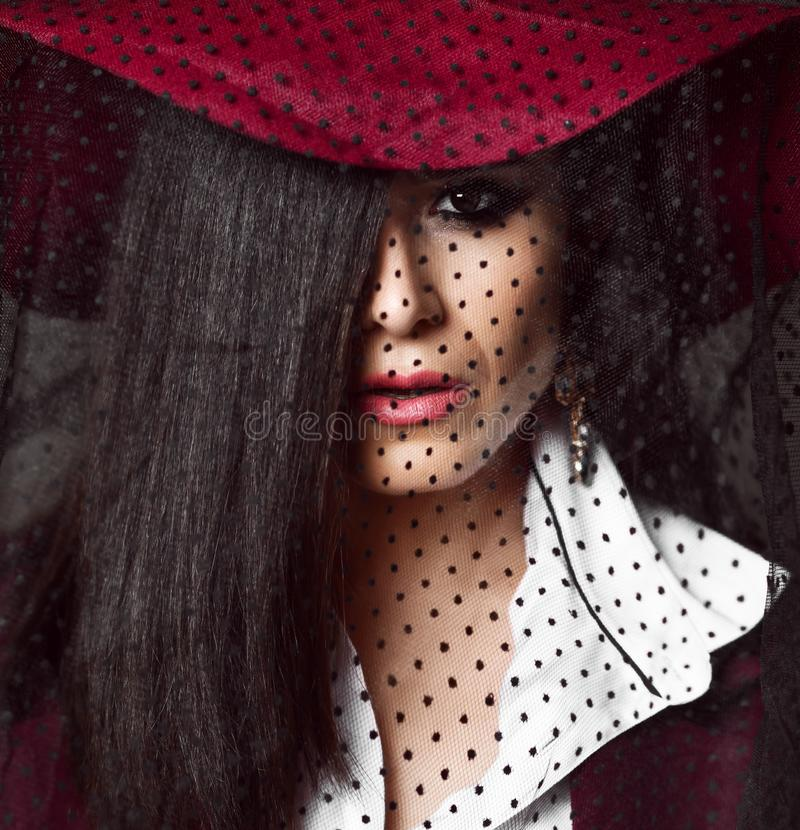 Full-face portrait of mysterious lady brunette in dark red hat with her veil down. And with half face hidden by her long straight hair royalty free stock images