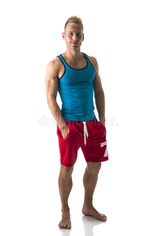 Full figure of muscular, young man standing confident barefeet, smiling stock photo