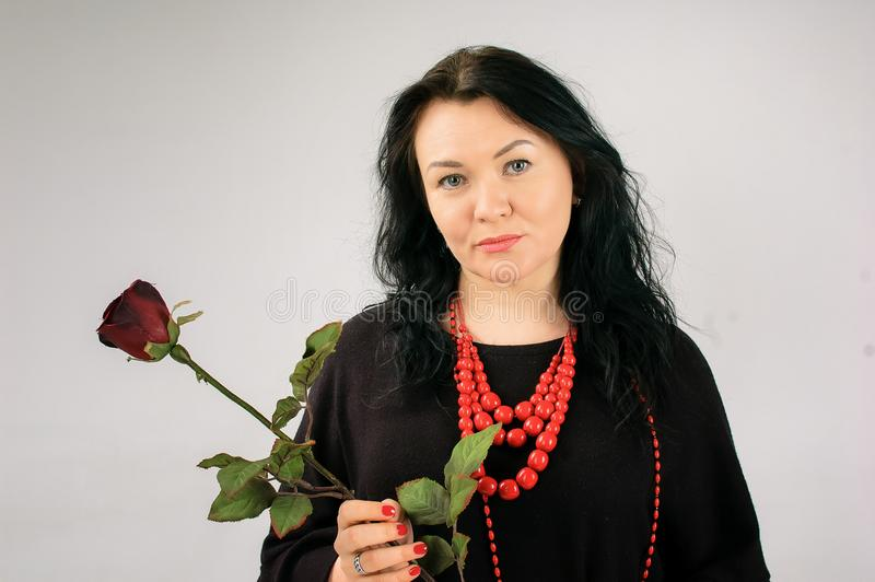 Full Figured Woman in Black Dress and Ethnic Necklace Holding Red Rose on Grey Background in Studio and Looking at the royalty free stock images