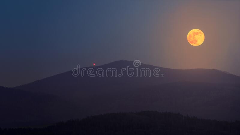 The full flower moon - May, 07, 2020. The rising moon over the mountain peaks of the Sudetes. A cloudless night allows observation of the astronomical stock photo