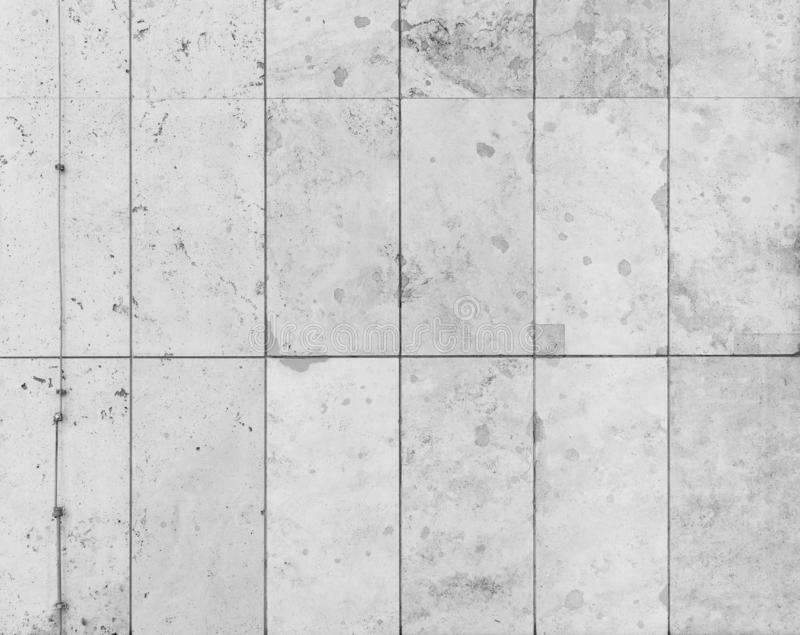 Modern light gray slab wall background. Full frame background of a modern and a bit broken wall or building exterior made of abstract stone slabs in black and stock image