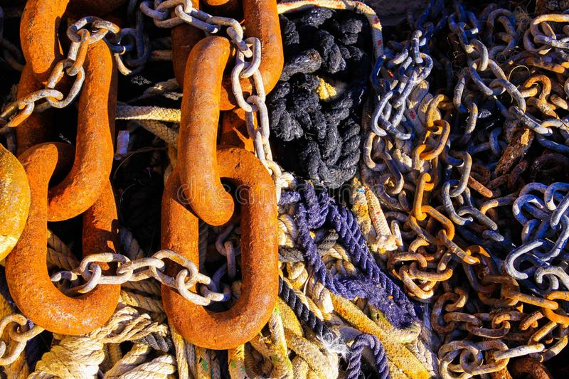 Full frame close up of old rusty brown anchor chain links on bunch of boat ropes in natural sun light stock images
