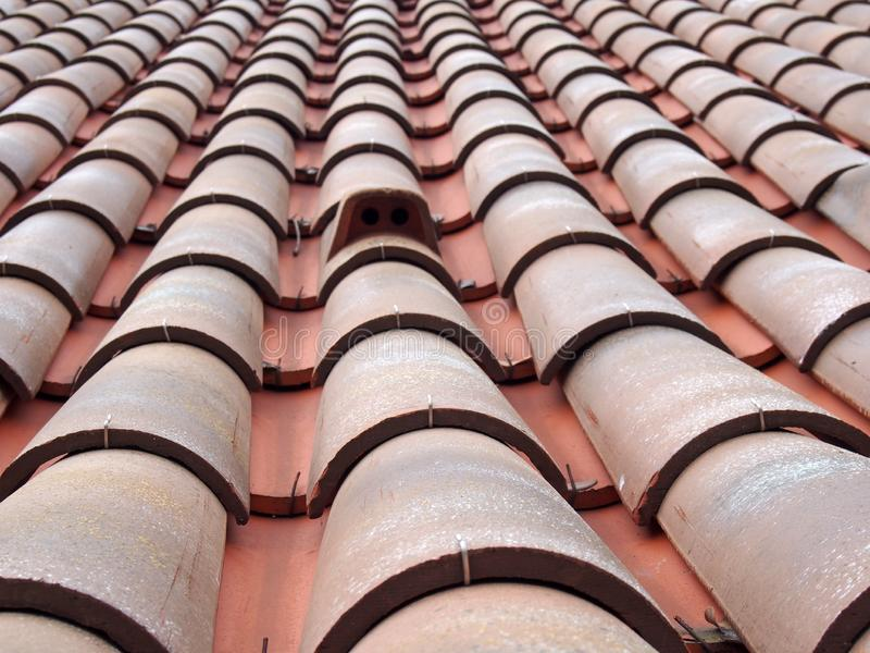 Full frame diminishing perspective view of an old roof with curved clay red tiles in lines with ventilation slots. A full frame diminishing perspective view of royalty free stock photo