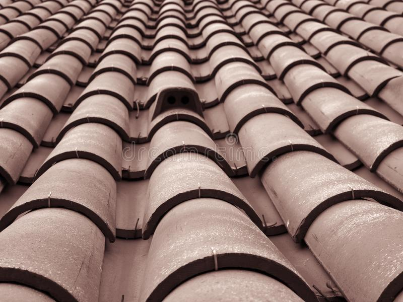 Full frame diminishing perspective view of an old roof with curved clay red tiles in lines with ventilation slots. A full frame diminishing perspective view of royalty free stock image