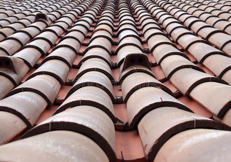 Full frame diminishing perspective view of an old roof with curved clay red tiles in lines with ventilation slots. A full frame diminishing perspective view of stock photography