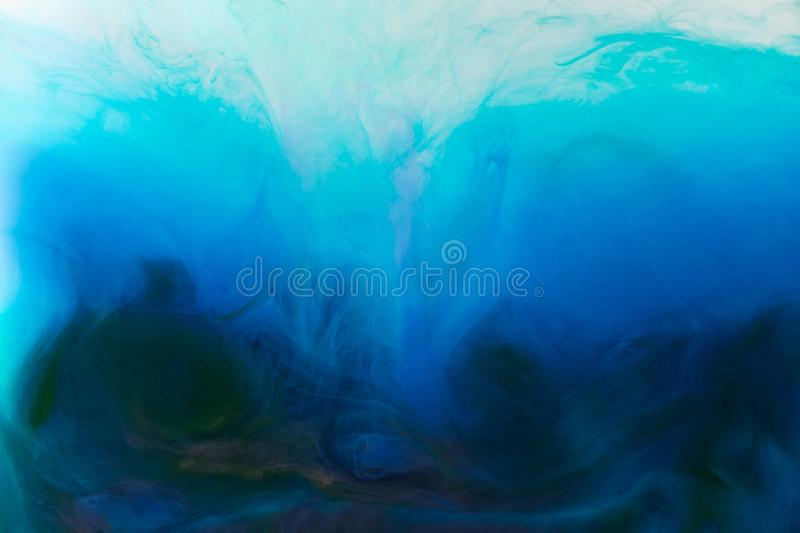 full frame image of mixing of blue, turquoise and black paints splashes in water stock image