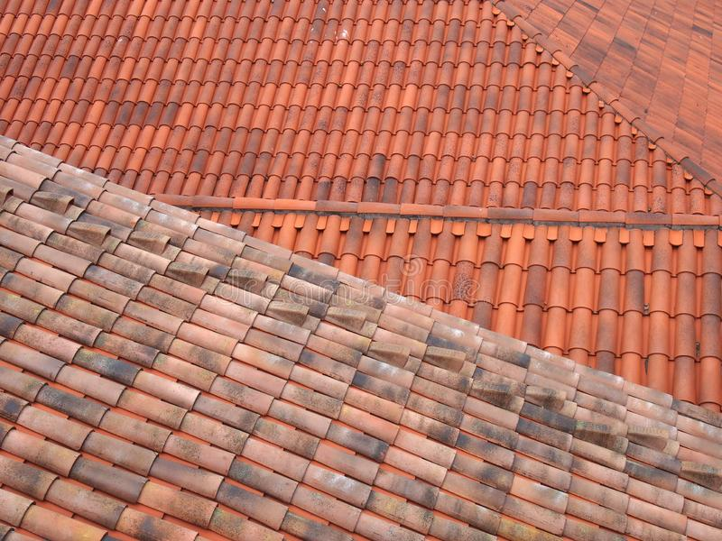 Full frame image of orange terracotta tiled roofs with diagonal traditional pantiles in lines and rows royalty free stock photography