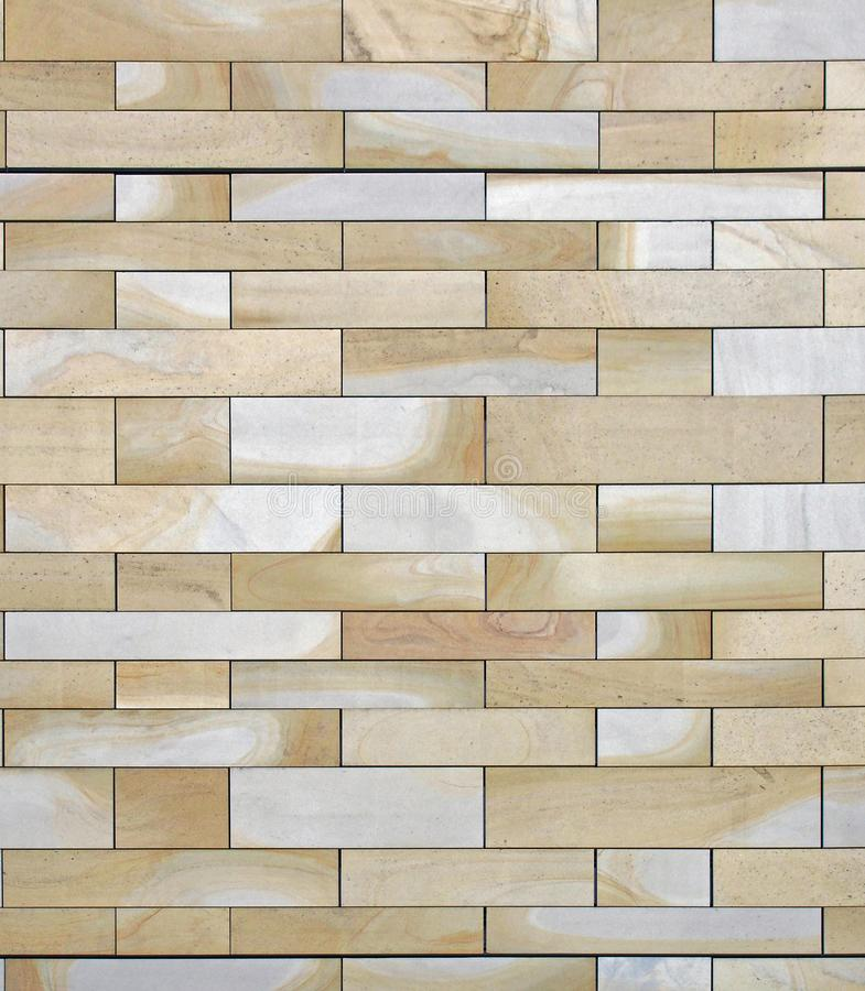 Full frame image of a wall made of large flat blocks of yellow and grey york stone with a marbled texture royalty free stock photo
