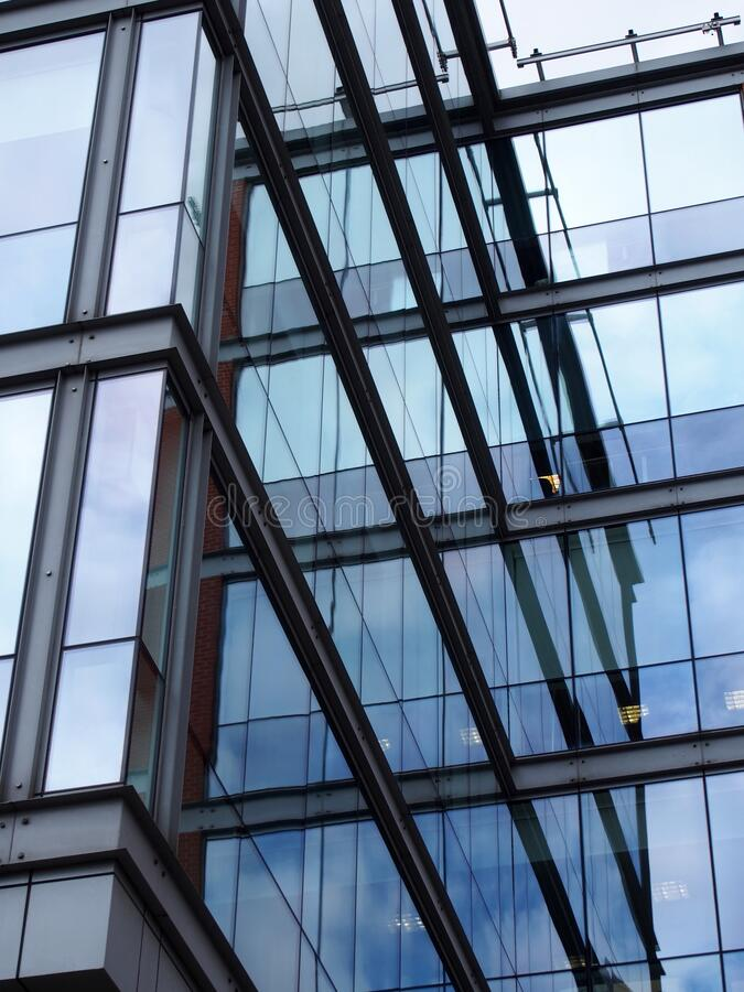Full frame modern office architecture abstract with geometric shapes and buildings and sky reflected in blue glass windows royalty free stock photography