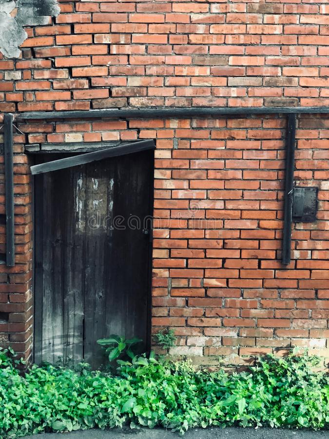 Full Frame Shot Of Brick Wall with a black old Wooden door. Full Frame Shot Of Brick Wall with an old Wooden door / Grass blocks the black ruined wooden door / royalty free stock photography
