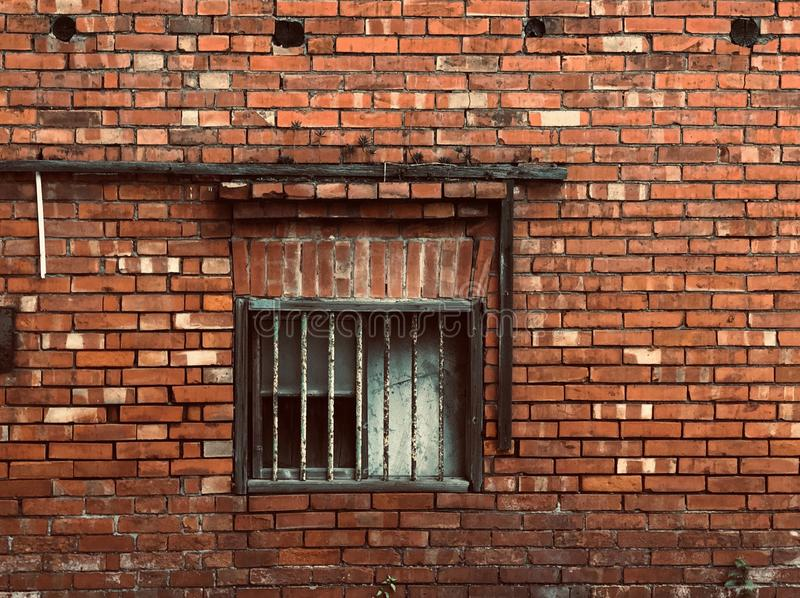 Full Frame Shot Of Brick Wall with a Rusty old window. / Ruined red brick house / Rusty iron railing./Painted wooden window frame royalty free stock photo