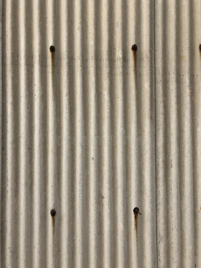 Full Frame Shot of Corrugated Asbestos tile board with rusty screws. / Building materials texture stock photography
