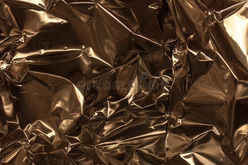 Full frame take of a sheeT of crumpled gold aluminum foil. Background royalty free stock photo