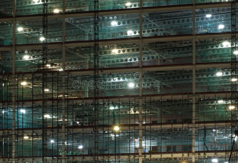 Full frame view of a large construction site at night illuminated by bright work lights with girders and construction hoists. A full frame view of a large royalty free stock images