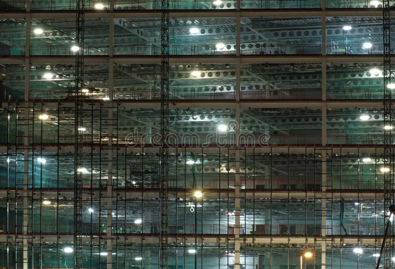 Full frame view of a large construction site at night illuminated by bright work lights with girders and construction hoists. A full frame view of a large stock photo