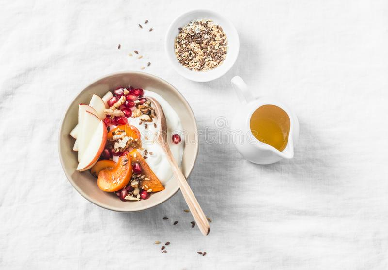 Full fruit and greek yogurt breakfast bowl. Persimmon, apple, walnuts, pomegranates and natural yogurt. Healthy food concept royalty free stock photo