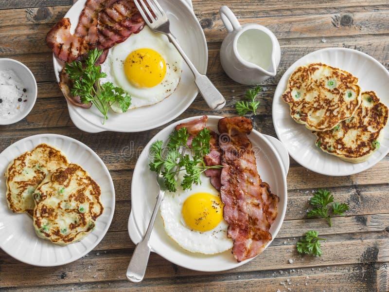 Full frukosttabell - stekte ägg med bacon och potatisar, gröna ärtor, purjolökpannkakor på en trätabell royaltyfria foton