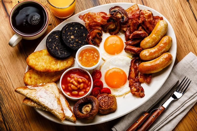 Full fry up English breakfast with fried eggs, sausages, bacon stock images