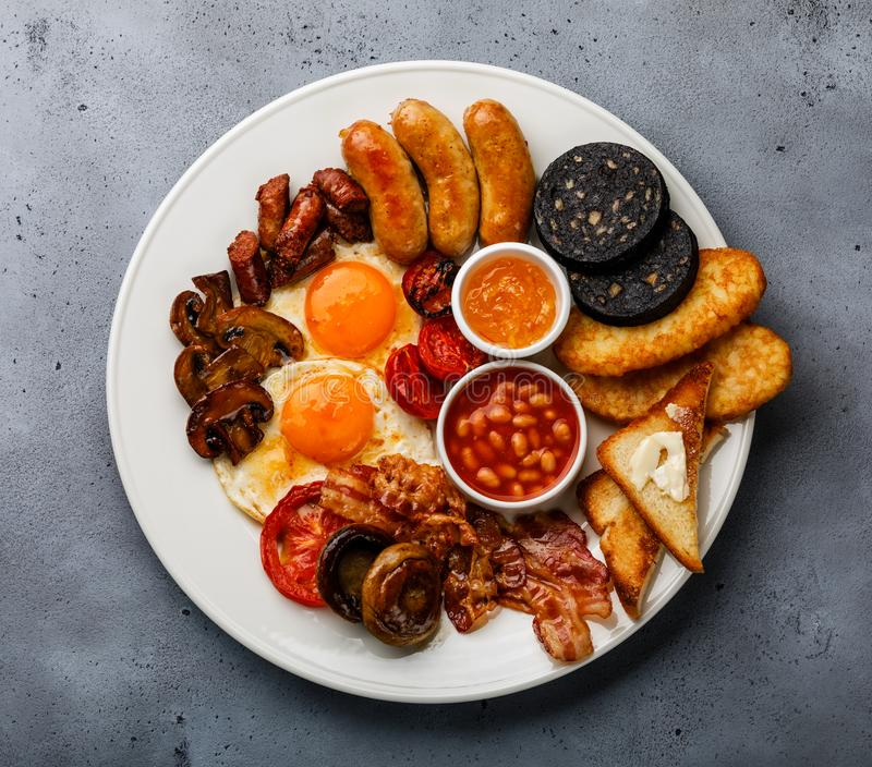 Full fry up English breakfast with fried eggs, sausages, bacon royalty free stock photography
