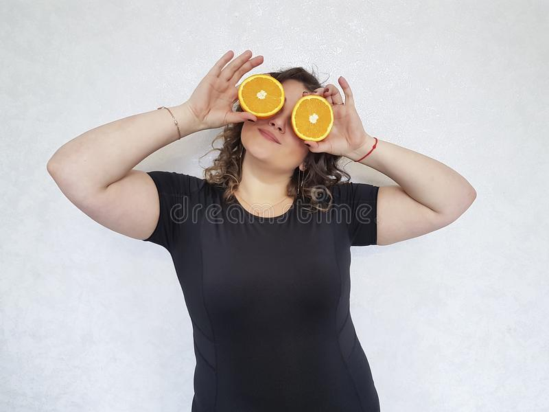 Full girl, an orange holds near the eyes stock image