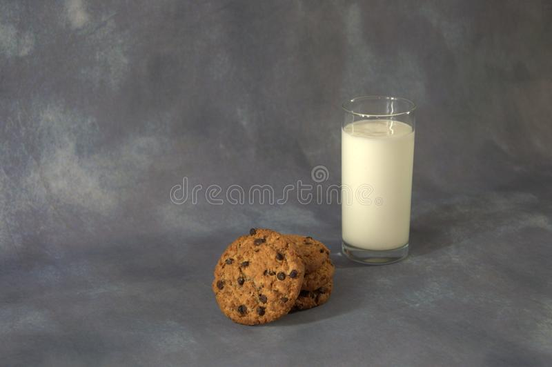Full glass cup of milk and a few oatmeal cookies with chocolate on a gray abstract background. Close-up royalty free stock photography