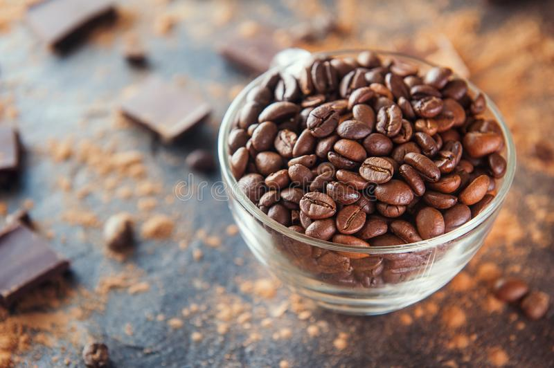 Full glass cup of Roasted coffee beans on the dark stone background with cocoa powder, pieces of chocolate and beans. Selective fo. Cus. Coffee love concept royalty free stock photography