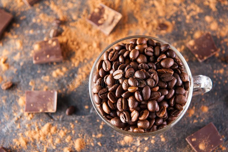 Full glass cup of Roasted coffee beans on the dark stone background with dissipate cocoa, pieces of chocolate and beans. Selective. Focus.Top view. Coffee love royalty free stock image
