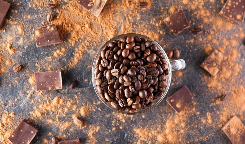 Full glass cup of Roasted coffee beans on the dark stone background with dissipate cocoa, pieces of chocolate and beans. Selective. Focus.Top view. Coffee love stock photos