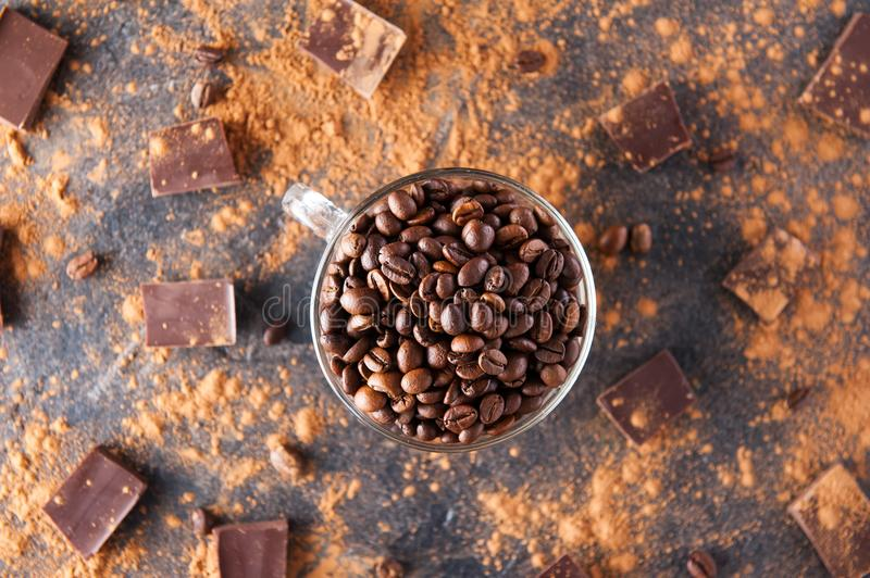 Full glass cup of Roasted coffee beans on the dark stone background with dissipate cocoa, pieces of chocolate and beans. Selective. Focus.Top view. Coffee love stock photo
