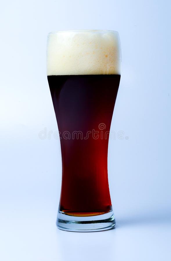 A full glass of dark beer with a large cap of froth. Slightly bluish background. Side view stock image