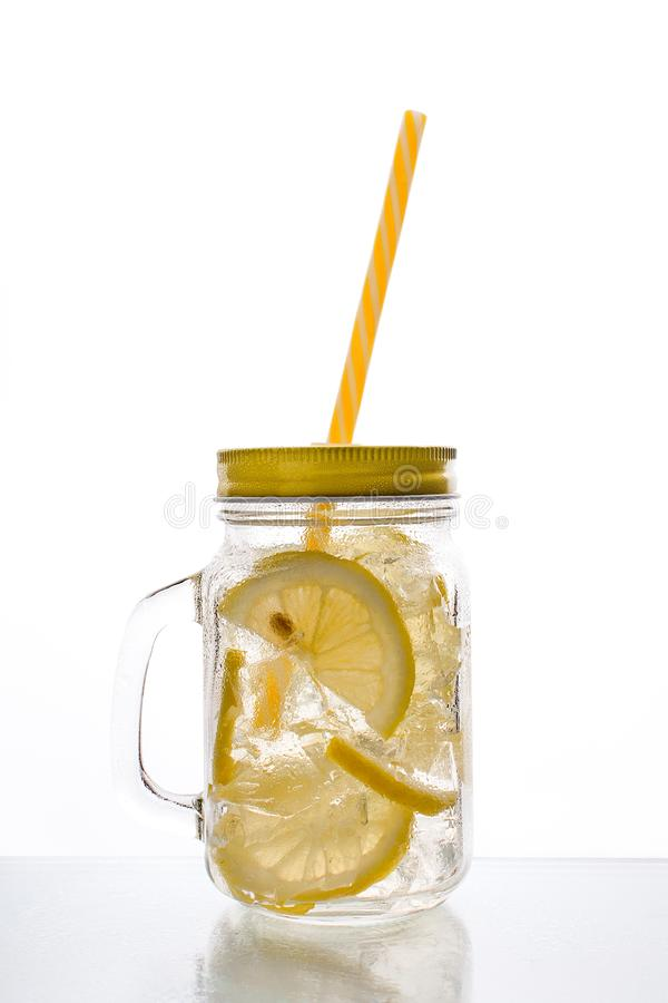 Full glass of fresh cool transparent water with lemon and ice royalty free stock images
