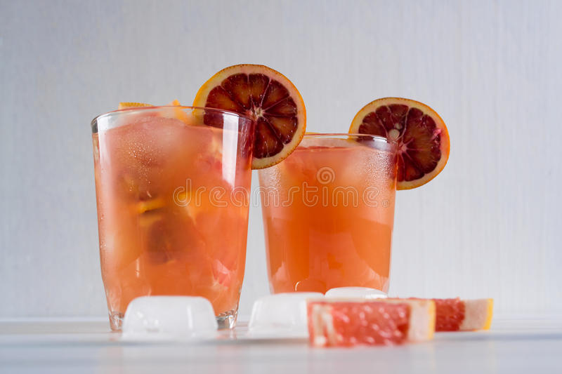 Full glass of grapefruit juice and glass of sliced fruit with ice royalty free stock photography