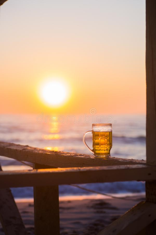 Full glass of light beer against backdrop of dawn on beach stock image