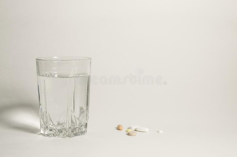 Full glass of water and a handful of pills stock photo
