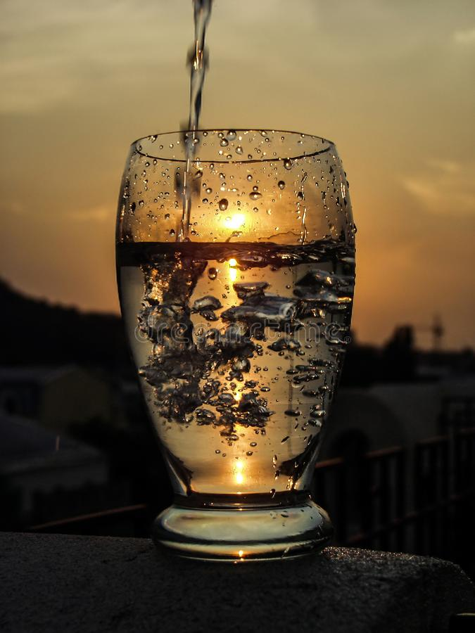 A full glass of water with a pouring waterjet and a sun downing stock photos