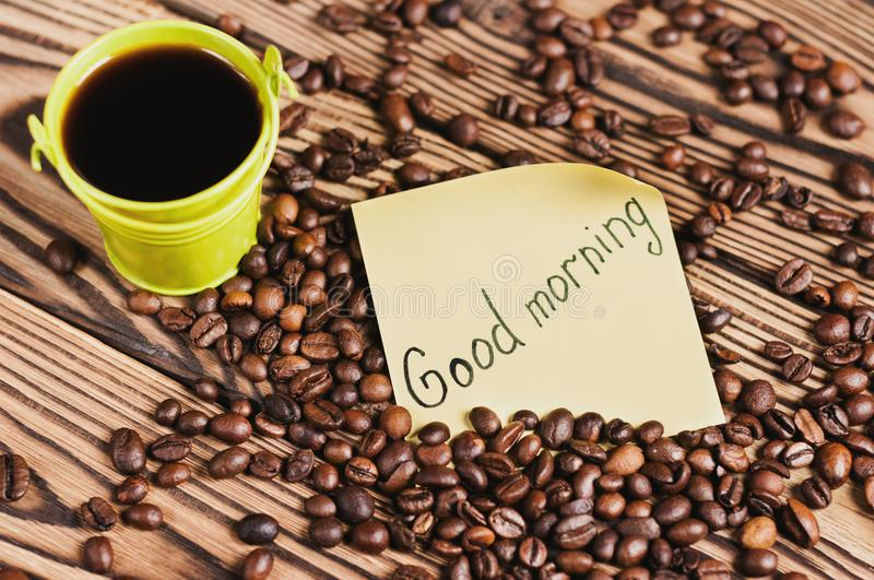 Full green metal bucket of black coffee near paper sticker with inscription good morning and scattered lot of roasted beans. On old worn wooden table stock photo