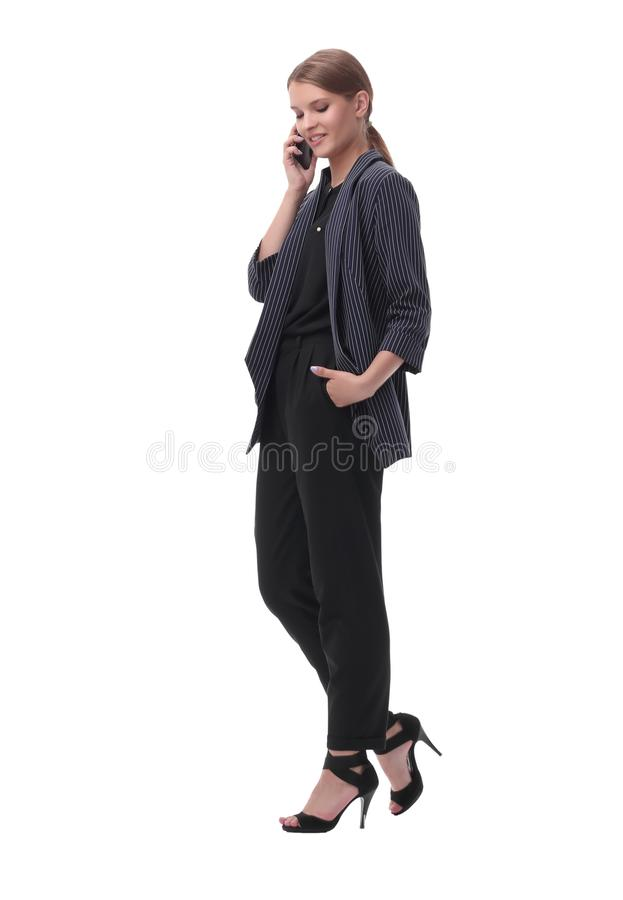 Confident young businesswoman talking on her smartphone. isolated on white. In full growth. confident young businesswoman talking on her smartphone. isolated on royalty free stock image
