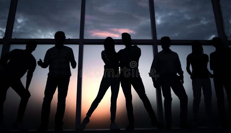 Group of young people in the background of a large window. In full growth.a group of young people in the background of a large window stock photos