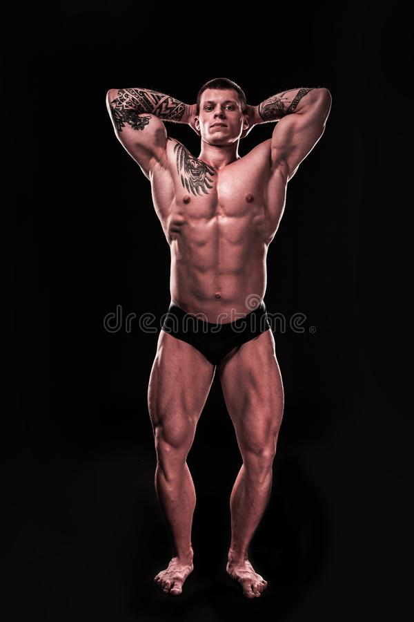 In full growth. handsome bodybuilder guy showing his inflated muscles stock photo