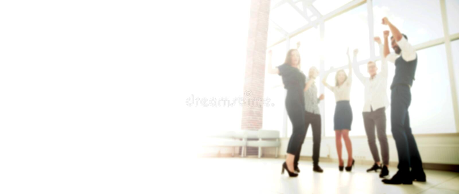 In full growth.happy business team standing in office in the blur royalty free stock image