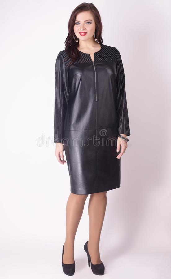 In full growth. modern woman model in a black leather dress .plus size. royalty free stock photography
