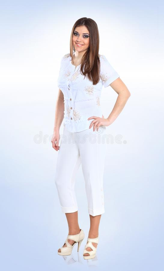 In full growth. portrait of a cute young woman in a white pantsuit royalty free stock photo
