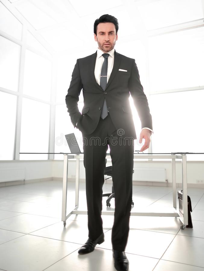 In full growth.serious businessman standing in a bright office. royalty free stock photos