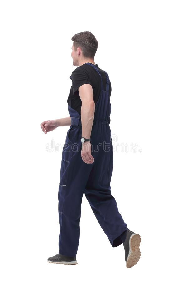 Smiling man in overalls goes forward.isolated on white stock images