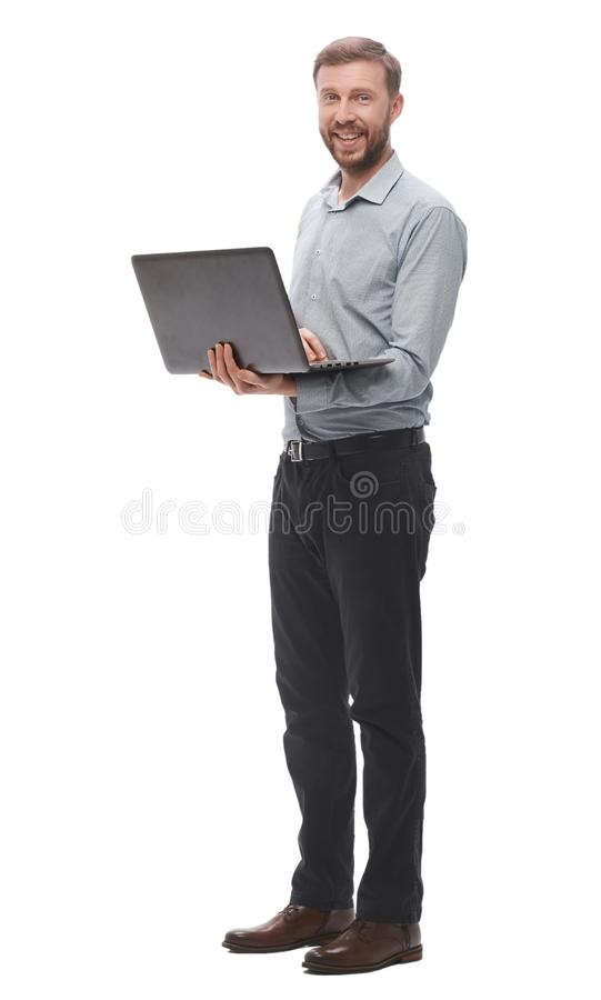 In full growth. smiling young businessman with laptop. stock images