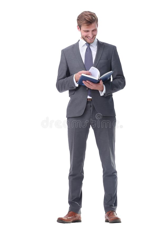 In full growth. young businessman making notes in a notebook. stock image