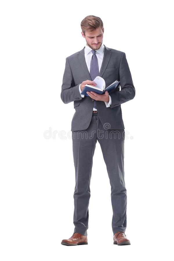 In full growth. young businessman making notes in a notebook. royalty free stock photo