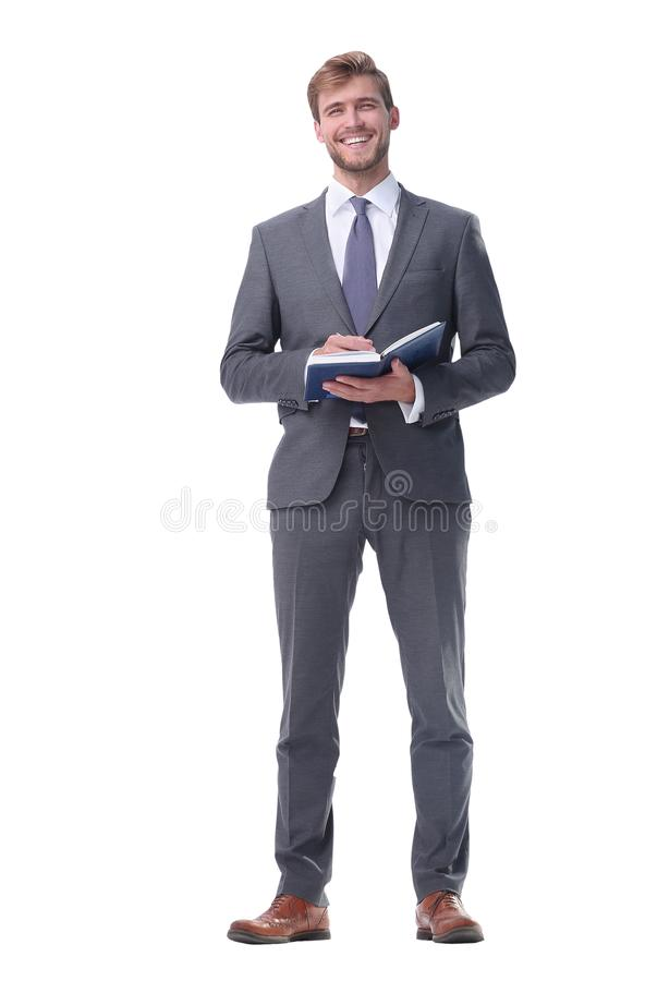 In full growth. young businessman making notes in a notebook. royalty free stock photography