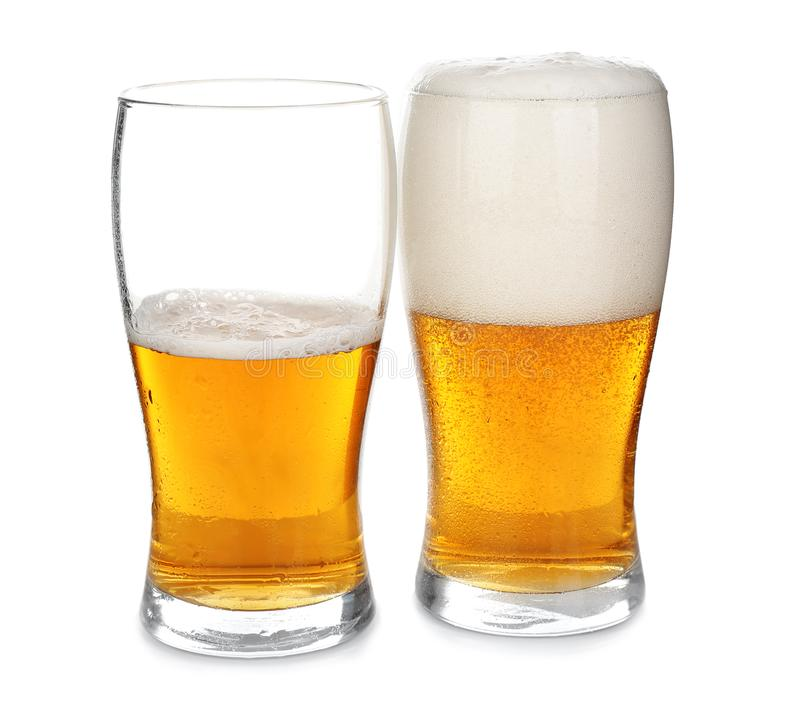 Full and half-filled glasses of cold beer on white background stock image